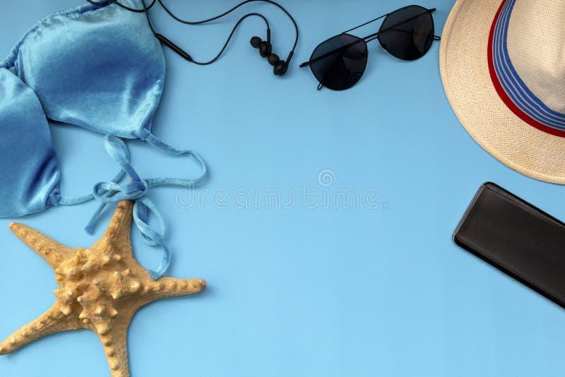 夏天旅行辅助部件在蓝色背景平展放置 泳装比基尼泳装、帽子、电话、太阳镜和海星为妇女的夏天 免版税库存照片
