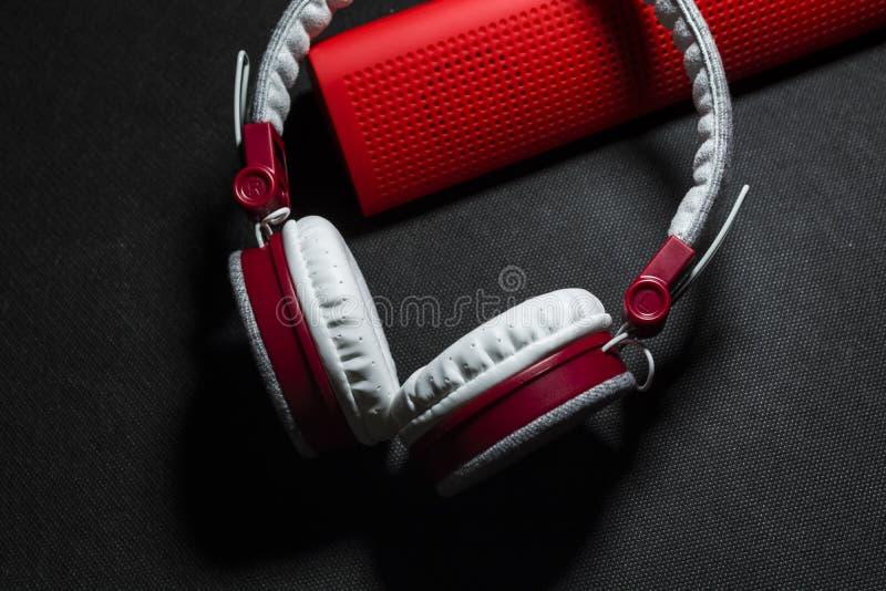 大便携式和多彩多姿的耳机和红色报告人听的音乐 白色和红颜色 在黑色背景 免版税库存图片