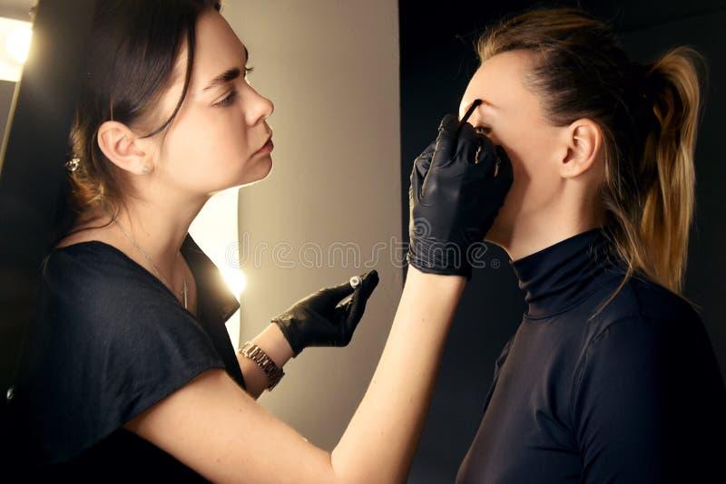 大师做眼眉 眼眉分片 女孩做在沙龙的眼眉 美好的眼眉形状 专业眼眉 库存图片