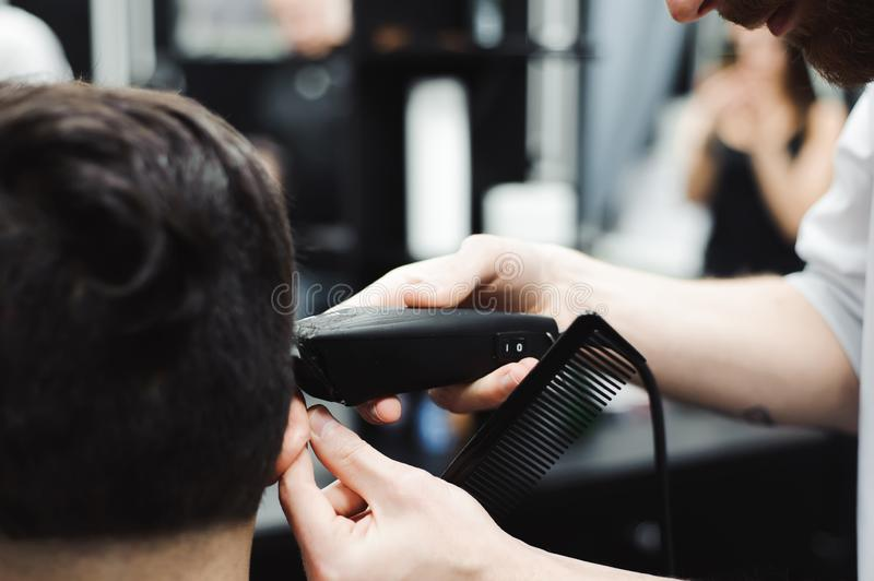 大师剪头发,并且人在理发店,美发师胡子做一个年轻人的发型 图库摄影