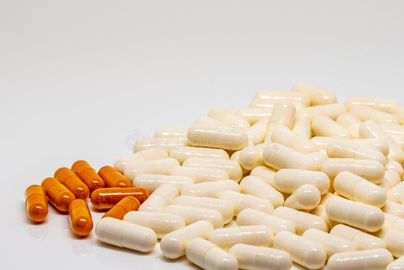 大束白色药片是在一束更小的橙色药片旁边 库存图片