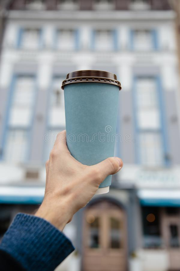 大模型广告:男性手在老镇背景中的拿着一个白纸杯子 图库摄影