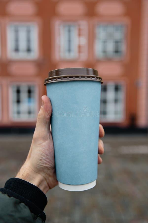 大模型广告:男性手在老镇背景中的拿着一个白纸杯子 免版税库存照片