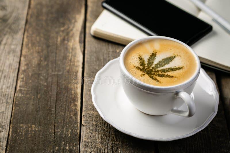 大麻咖啡-在咖啡泡沫的大麻叶子 免版税库存图片