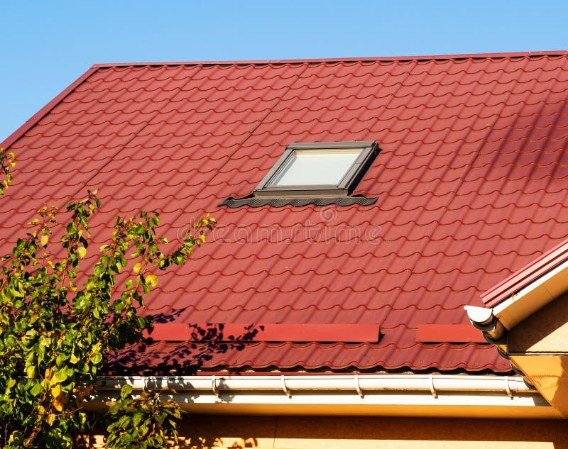 天窗和snowguards特写镜头在赤土陶器金属瓦屋顶 免版税库存图片