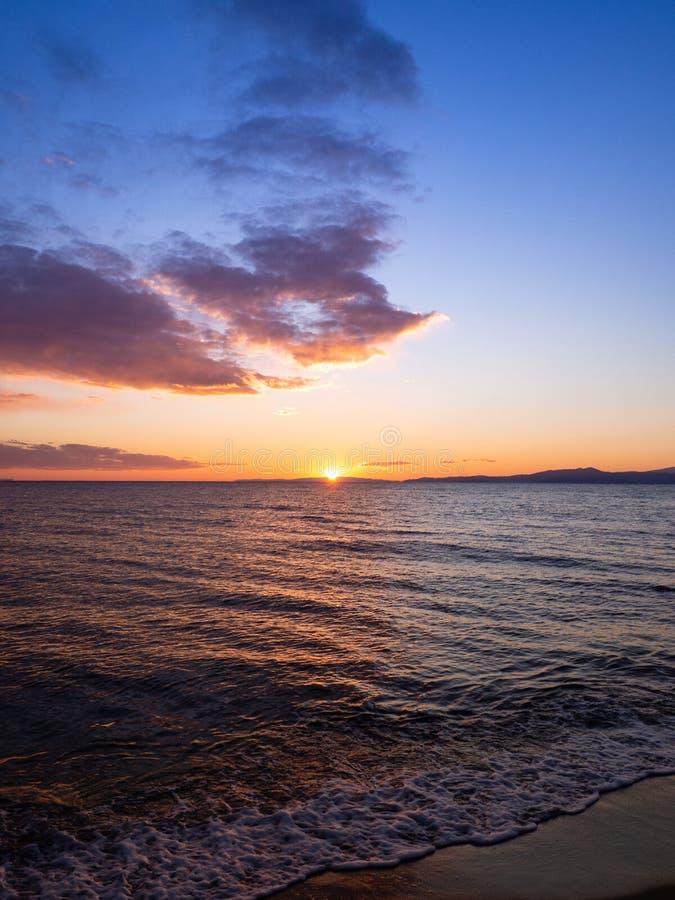 太阳在海滩设置在卡瓦拉,希腊 免版税库存照片