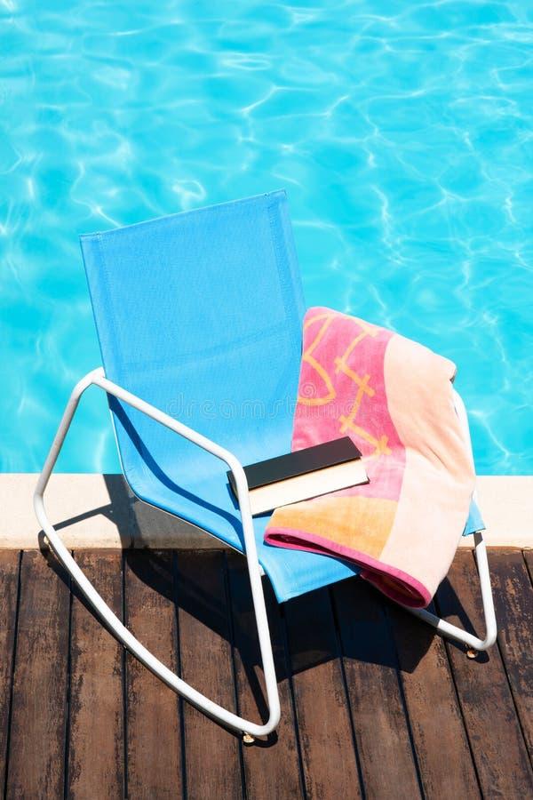 太阳椅子场面与海滩毛巾和书的在游泳场 免版税库存照片