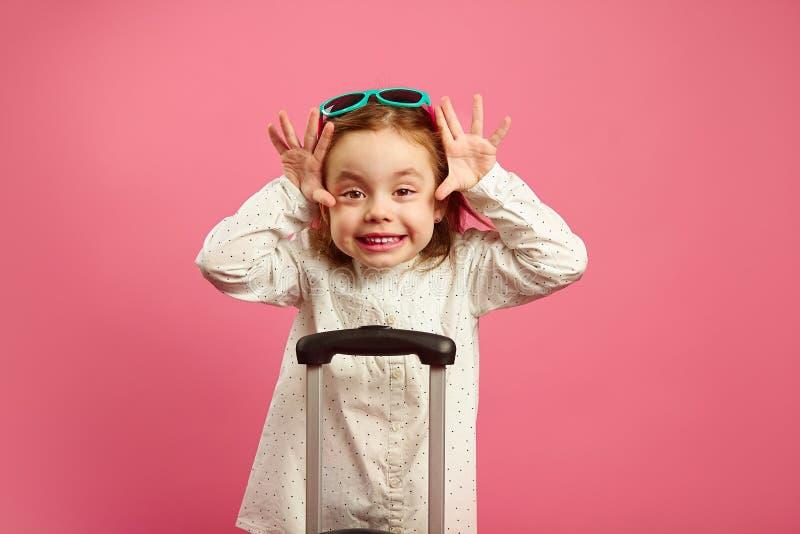 太阳镜的逗人喜爱的女孩做滑稽的疯狂的面孔,大棕色眼睛,并且举胳膊在隔绝的手提箱附近站立 图库摄影