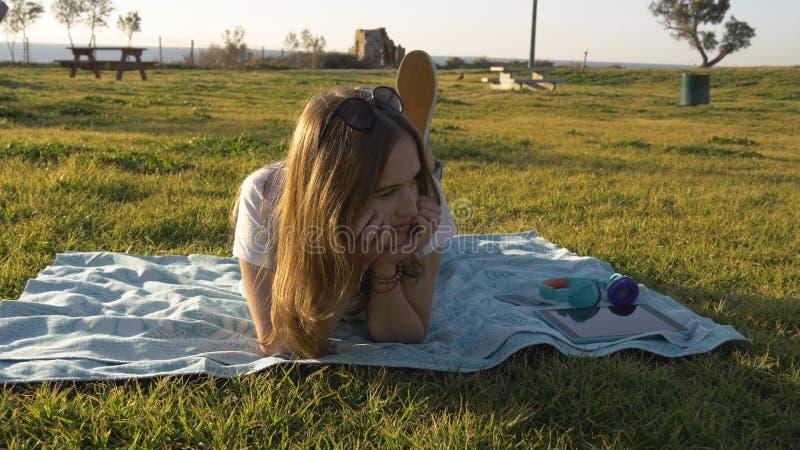 太阳镜错过的年轻女性在绿色公园 免版税库存图片