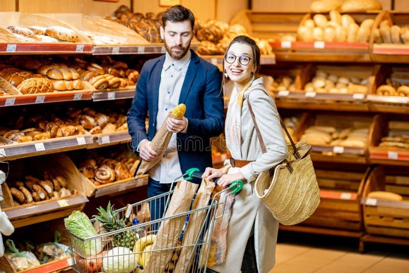 夫妇买的面包店在超级市场 免版税库存图片