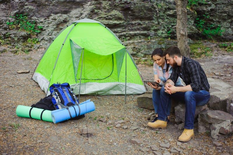 夫妇野营在山的,帐篷,在旅游轨道附近的两个背包在山 免版税库存图片