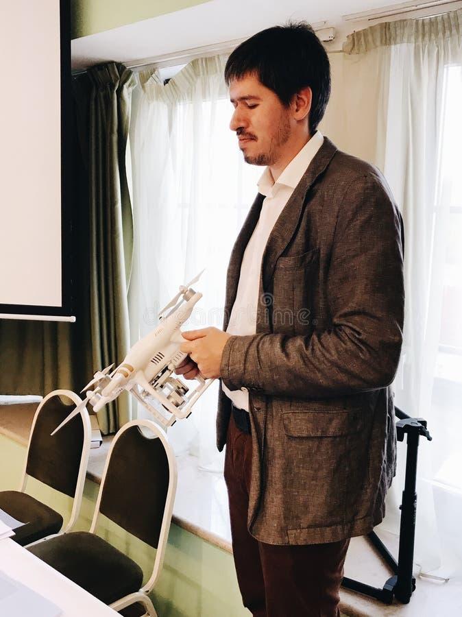 夹克的年轻人有白色quadcopter的 库存照片