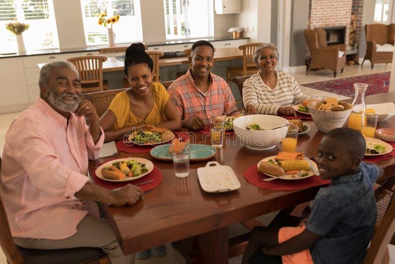 多代的家庭有膳食一起在饭桌在家 库存照片