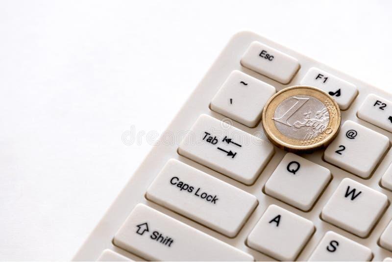 多少做程序员在欧洲赢得 欧元硬币在与第一的钥匙说谎在键盘 财务的概念 免版税图库摄影