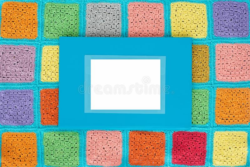 多彩多姿的正方形被钩编编织物的鞋带桌布在蓝色背景,顶视图,文本的,自然羊毛地方装饰 免版税库存图片