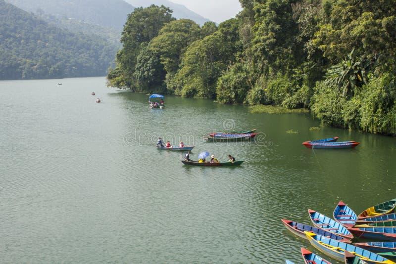 多彩多姿的木小船的人们在反对绿色密林的背景的湖 免版税库存图片