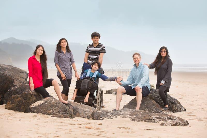 多种族专辑需要家庭坐沿海滩的大岩石 免版税库存照片