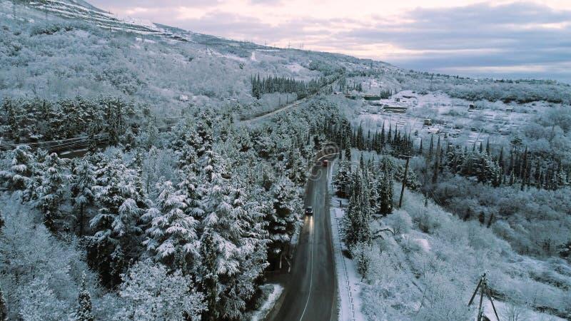 多雪的森林和a的继续前进冬天路的天线和汽车 射击 路的鸟瞰图通过冬天森林 免版税库存照片