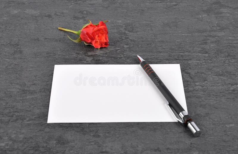 备忘录、笔和红色玫瑰在板岩 库存照片