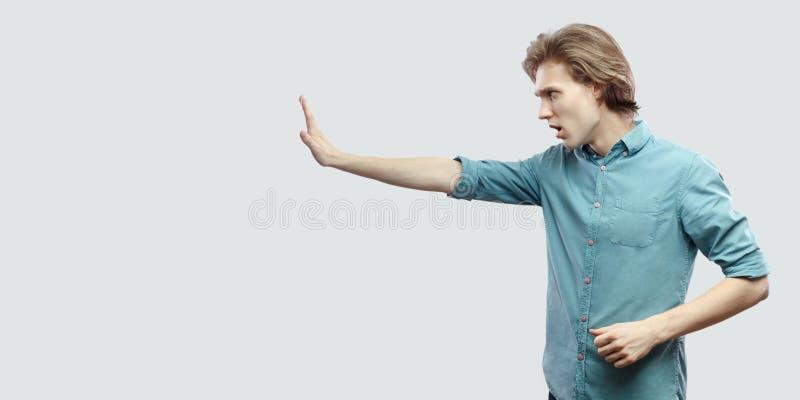 外形严肃的英俊的长发白肤金发的年轻人侧视图画象蓝色偶然衬衣身分的与中止手势 库存图片