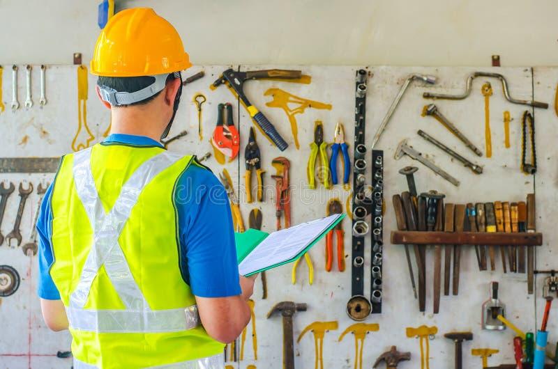 头戴防护安全帽的年轻亚洲男性工程师或建筑师待办卷宗在许多不同的生锈的老工具附近 免版税图库摄影