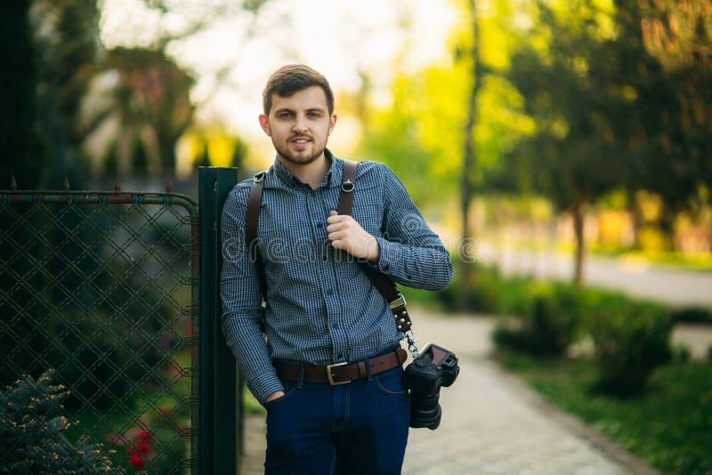 外面专业摄影师画象  人用途最好照相机和皮带 英俊的确信的年轻人 库存图片