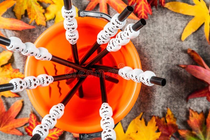 头骨塑料鸡尾酒绞拌器、秸杆在把戏或款待南瓜桶 免版税库存图片