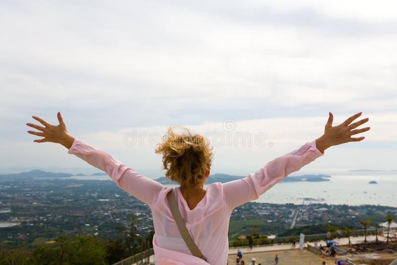 女孩举了她的手用在普吉岛海岸的背景的不同的方向  免版税库存图片