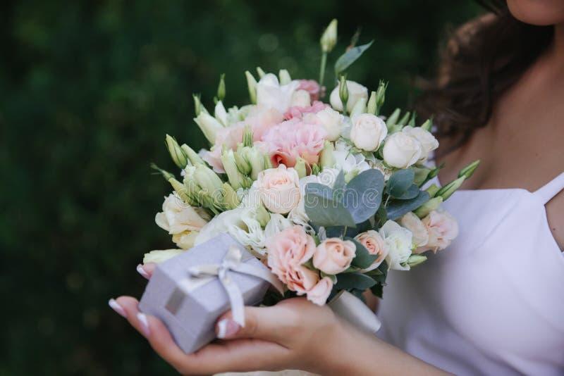 女孩举行花束和圆环箱子在手上 法式修剪 女性在白色礼服打扮 免版税库存照片