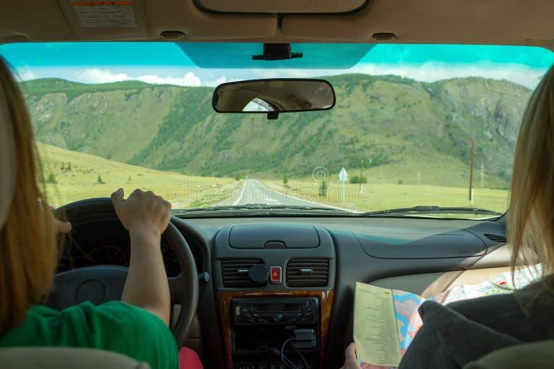 女孩乘坐在乘客座位和神色的汽车在寻找期望路线的纸地图并且表明路 图库摄影