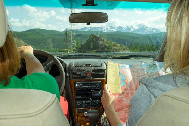 女孩乘坐在乘客座位和神色的汽车在寻找期望路线的纸地图并且表明路 库存图片