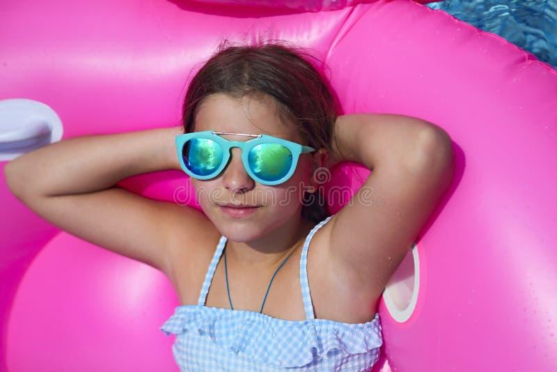 女孩佩带的太阳镜画象在可膨胀的火鸟游泳浮游物的 免版税库存照片