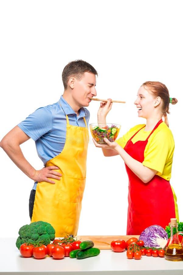 女孩对待她的恋人与新鲜蔬菜沙拉,他们在白色一起烹调 免版税库存图片