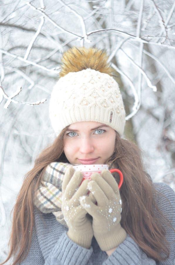 女孩在与杯子的冬天 免版税图库摄影