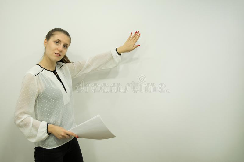 女孩在一只手上时的提出某事,当站立在左边对白色墙壁拿着板料 库存图片