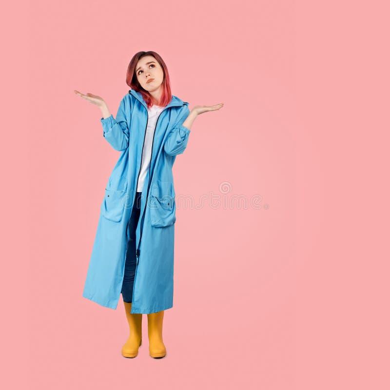 女孩在一双外套和胶靴打扮,周道地查寻,耸肩 免版税图库摄影