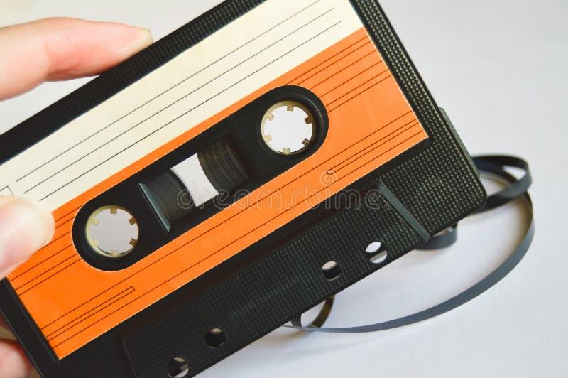 女孩在她的手橙色老卡型盒式录音机举行 关闭 免版税库存照片