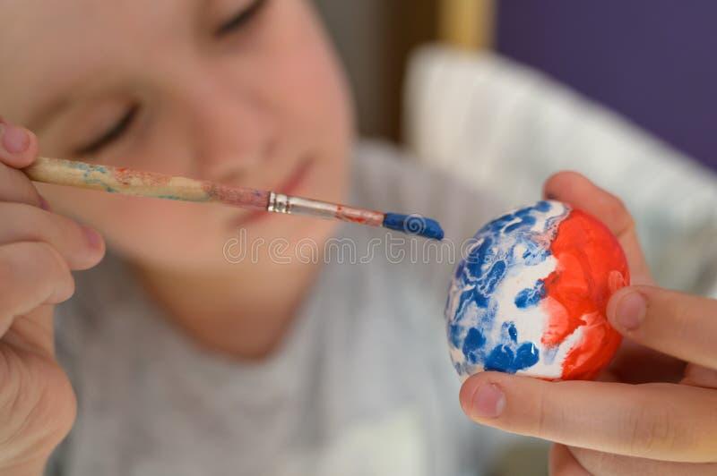 女孩在家绘复活节彩蛋 图库摄影