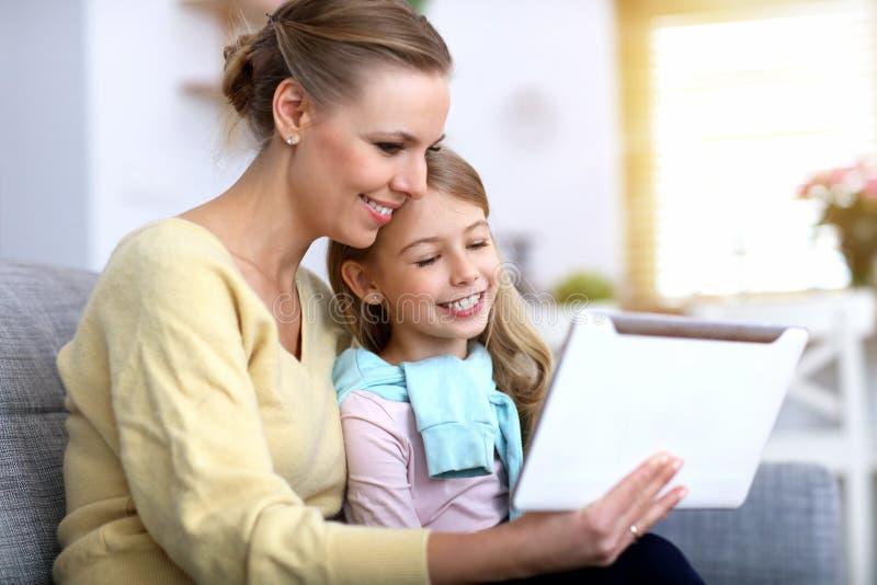 女孩和她的使用片剂的妈妈,当在家时坐沙发 免版税图库摄影