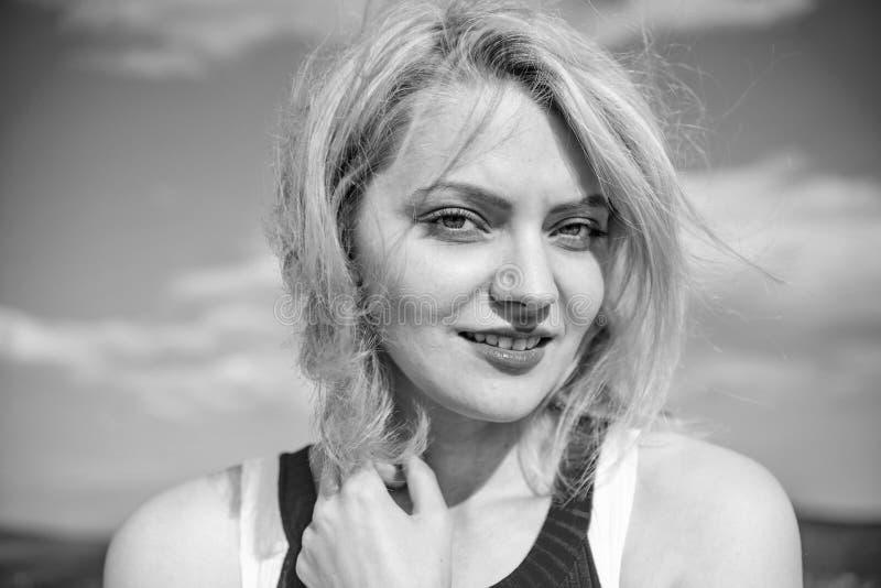 女孩喜欢与温暖的阳光看起来轻松的蓝天背景 感受和谐和和平 容易的作为 妇女金发碧眼的女人 免版税库存照片