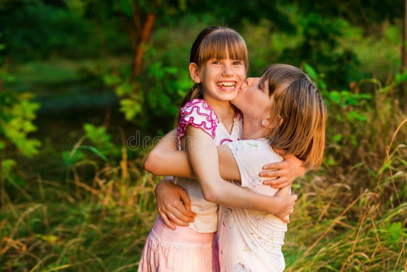 女孩是非常愉快的她有姐妹 拥抱逗人喜爱的女孩的爱恋的姐妹显示爱关心支持 免版税图库摄影