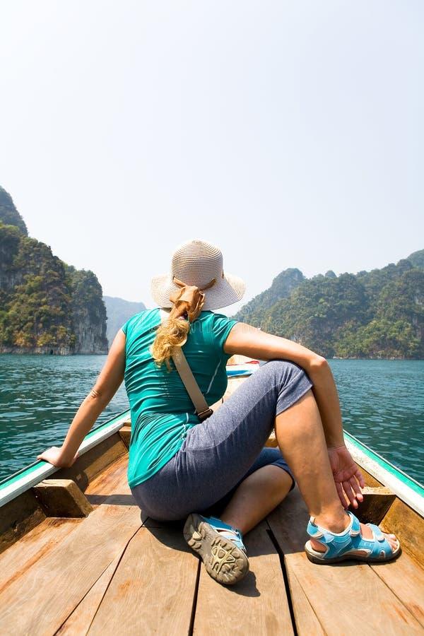 女孩旅客看异乎寻常的海岛,当坐在小船时 免版税库存照片