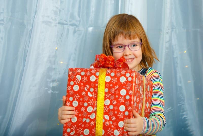 女孩拿着有礼物的Masha一个箱子 库存图片