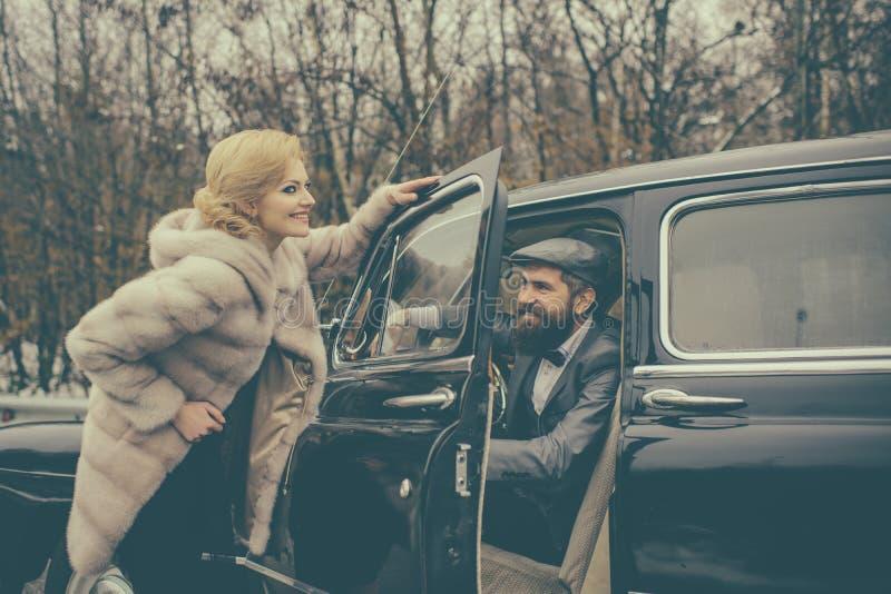 女孩的伴游由安全的 有胡子的男人和性感的妇女毛皮大衣的 在爱的夫妇在浪漫日期 减速火箭的收藏 库存照片