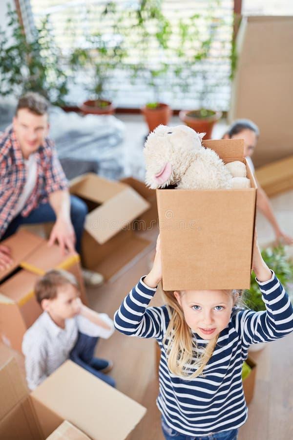 女孩运载与可爱的玩具的纸板 免版税库存照片