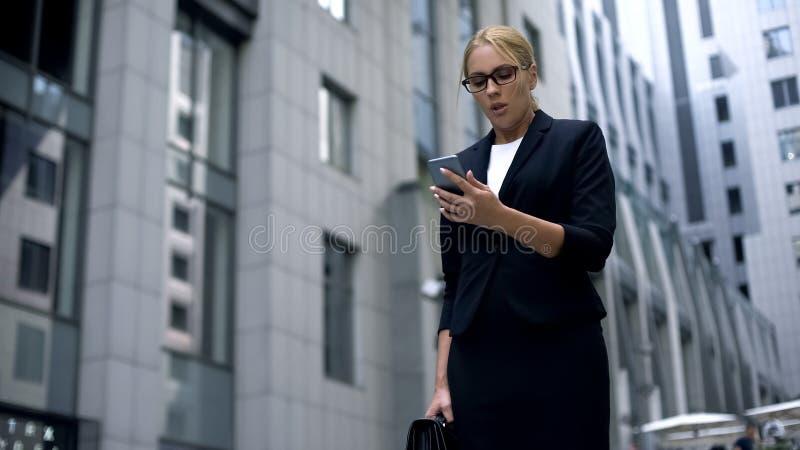 女实业家观看的成交在网上通过智能手机,担心投资 免版税库存图片