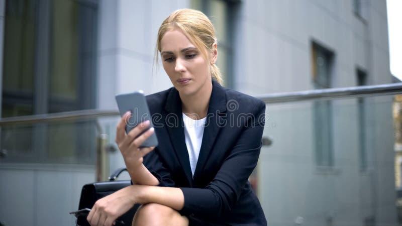 女实业家让烦恼与在智能手机的消息,麻烦在工作,消沉 库存照片