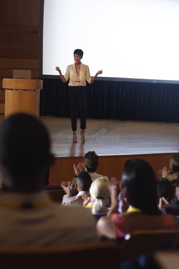 女实业家身分和给介绍在观众前面在观众席 库存照片