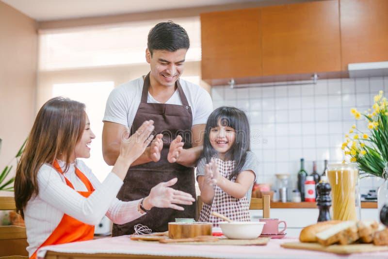 女儿帮助父母准备烘烤家庭观念 免版税库存图片