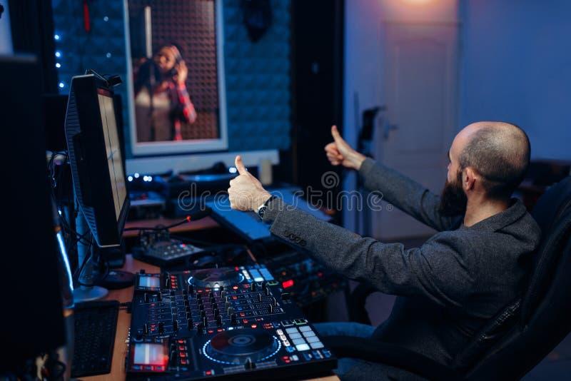 女歌手在记录的屋子里和录音师 图库摄影